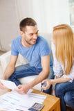 Lächelnde Paare mit Papieren und Taschenrechner zu Hause Lizenzfreies Stockfoto