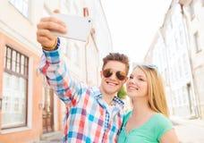 Lächelnde Paare mit Smartphone in der Stadt Stockbilder