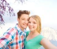 Lächelnde Paare mit Smartphone in der Stadt Lizenzfreie Stockfotos