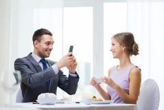 Lächelnde Paare mit Sushi und Smartphones Lizenzfreies Stockbild