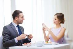 Lächelnde Paare mit Sushi und Smartphones Stockbild