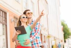 Lächelnde Paare mit Tabletten-PC in der Stadt Stockfotos