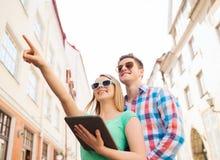 Lächelnde Paare mit Tabletten-PC in der Stadt Lizenzfreies Stockbild