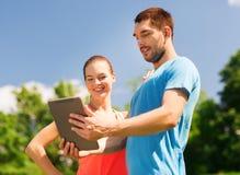 Lächelnde Paare mit Tabletten-PC draußen Stockfotografie