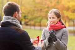 Lächelnde Paare mit Verlobungsring in der Geschenkbox Stockbilder