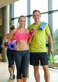 Lächelnde Paare mit Wasserflaschen in der Turnhalle Stockfotos