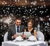 Lächelnde Paare am Restaurant Stockbild