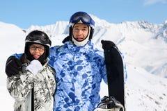 Lächelnde Paare stehen mit Snowboard und Skis Lizenzfreies Stockfoto