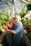 Lächelnde Paare unter Anlagen am Gewächshaus Stockfotografie