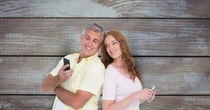 Lächelnde Paare unter Verwendung des intelligenten Telefons gegen hölzerne Wand Lizenzfreies Stockfoto