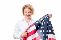 Lächelnde patriotische Frau, die Flagge Vereinigter Staaten hält USA feiern am 4. Juli Stockfotografie