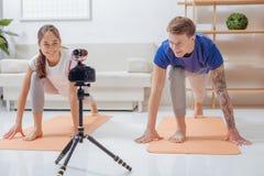 Lächelnde positive Bloggers, die Übungen vor einer Kamera tun Stockfotos