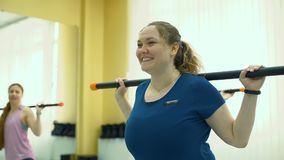 Lächelnde pralle Frau, die Übungen mit Barbell tut stock footage