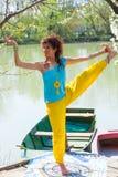 Lächelnde Praxisyoga-Balancenlage der jungen Frau im Freien durch das gesunde Lebensstilkonzept des Sees stockfotos