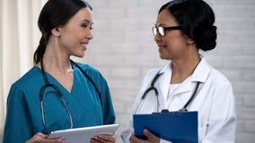 Lächelnde Privatklinikarbeitskräfte, die miteinander, sicher im Professionalismus lächeln lizenzfreie stockbilder