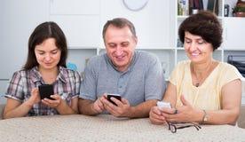 Lächelnde reife Eltern mit der Tochter, die mit Telefonen sitzt Stockfoto