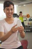 Lächelnde reife Frau, die ihren Handy in der Turnhalle, die Kamera betrachtend verwendet Lizenzfreies Stockfoto