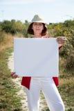 Lächelnde reife Frau, die leeres Zeichen für das Necken in der Landschaft zeigt Stockbild