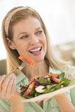 Lächelnde reife Frau, die Salat zu Hause isst Lizenzfreies Stockfoto