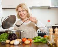 Lächelnde reife Frau, die Suppe kocht Stockbilder