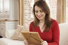 Lächelnde reife Frau, die zu Hause Bilderrahmen betrachtet Stockfotos