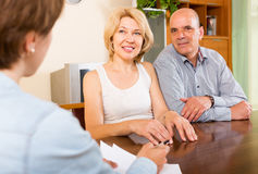 Lächelnde reife Paare, die mit Angestelltem sprechen Stockbilder