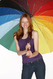 Lächelnde rote Hauptfrau mit Regenbogen-Regenschirm Stockfotos
