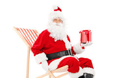 Lächelnde Santa Claus, die auf einem Strandstuhl und -c$halten eines Geschenks sitzt stockfotos