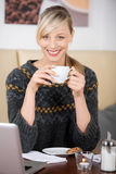Lächelnde schöne blonde Frau, die einen Kaffee trinkt Stockfotos