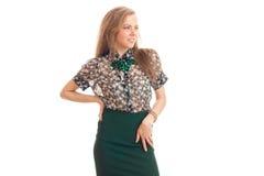 Lächelnde schöne Blondine in der bunten Kleidung hält eine Hand auf der Seite und die Aufstellung im Studio Stockfoto