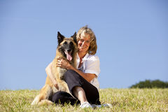 Lächelnde schöne Frau, die ihren Hund umarmt stockbilder