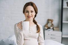 lächelnde schöne Holdingtasse tee der schwangeren Frau und das Betrachten der Kamera lizenzfreie stockfotografie