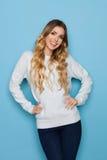 Lächelnde schöne junge blonde Frau in der blauen Pastellstrickjacke und in den Jeans Lizenzfreie Stockbilder