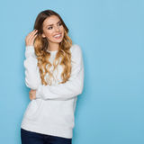 Lächelnde schöne junge blonde Frau in der blauen Pastellstrickjacke und in den Jeans schaut weg Stockfotos