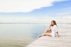 Lächelnde schöne junge Frau, die auf einem Pier sitzt und auf t spricht Stockfotografie