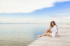 Lächelnde schöne junge Frau, die auf einem Pier und der Anwendung eines mobi sitzt Lizenzfreies Stockfoto
