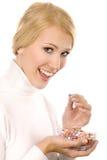 Lächelnde schöne junge Frau, die bunte Pillen isst Stockfotografie