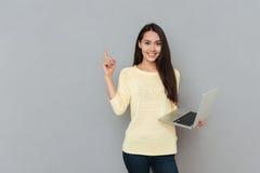 Lächelnde schöne junge Frau, die Laptop hält und weg zeigt Lizenzfreie Stockbilder