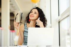 Lächelnde schöne junge Frau, die Laptop verwendet und auf Mobile spricht Stockfotografie