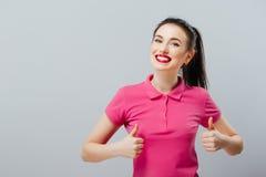 Lächelnde schöne junge Frau im rosa Minikleid, das sich Daumen und das Blinzeln zeigt Lizenzfreie Stockfotos