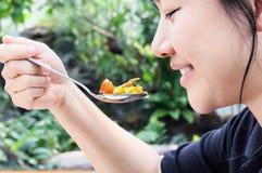 Lächelnde schöne lange schwarzes essende Haar Asiatinnen, Handfang Stockbilder