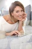 Lächelnde Schönheit, die Tablette auf Sofa verwendet Lizenzfreie Stockfotografie