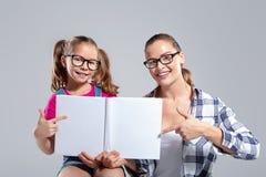 Lächelnde Schönheit und ihre Tochter in den Gläsern mit Buch stockbilder