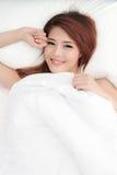 Lächelnde schüchterne asiatische Frau unter einer Daunendecke Stockfotos