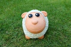 Lächelnde Schafpuppe auf dem Gras Stockfotos