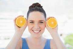 Lächelnde schlanke Frau in der Sportkleidung, die Scheiben der Orange hält Stockfotografie
