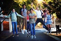 Lächelnde Schulkinder, die Spaß auf Straße im Campus haben lizenzfreie stockfotografie