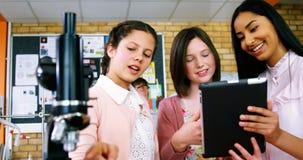 Lächelnde Schulmädchen, die über digitaler Tablette im Labor sich besprechen stock video footage