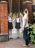 Lächelnde Schulmädchen, die zur Schule gehen und zu ihrer Mutter wellenartig bewegen Lizenzfreie Stockfotos
