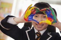 Lächelnde SchulmädchenFingermalerei, Abschluss oben auf Händen Stockbild